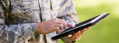 man in army uniform using tablet